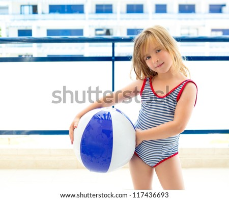 Blond kid girl with swimsuit with summer blue ball in balconade - stock photo