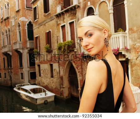 Blond lady against Venice canal. - stock photo
