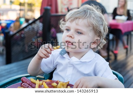 Blond little boy eating french fries in summer, outdoors - stock photo