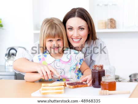 Blond little girl and her mother preparing toasts in the kitchen - stock photo
