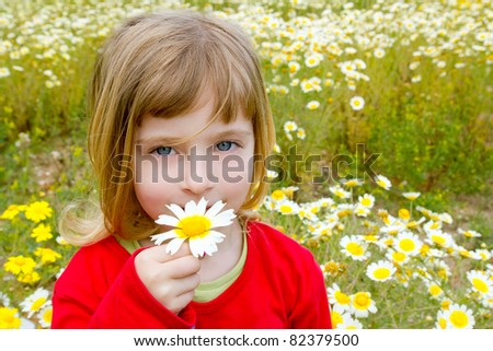 blond little girl smelling a daisy spring flower in meadow field - stock photo
