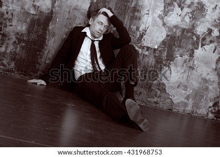 Blond man in depression sitting on the floor. Dressed in a formal classic suit. Vintage Black and White colour graded. - stock photo