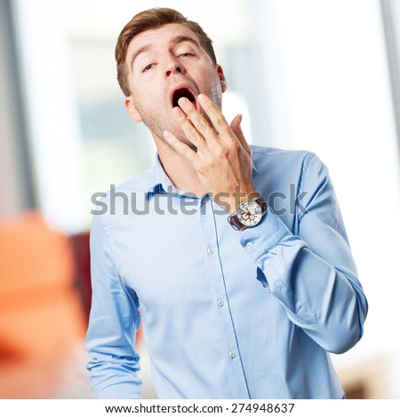 blond man yawning - stock photo