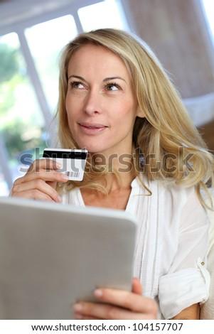 Blond mature woman doing online shopping - stock photo