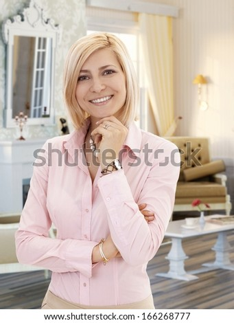 Blond mid-adult woman in stylish elegant living room at home, smiling. - stock photo