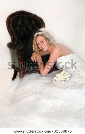 Blond model in wedding dress has soft curls and is wearing a radiant smile.  White roses lay across her lap.  Antique chair serves as prop. - stock photo