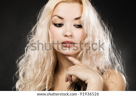 Blond model on black background, studio portrait - stock photo