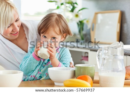 Blond mother and daughter having breakfast in the kitchen - stock photo