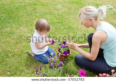 Blond Mother showing her daughter a purple flower in their garden - stock photo