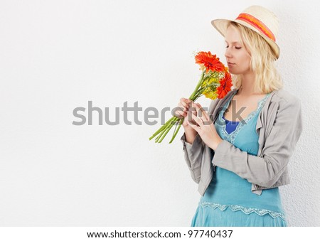 Blond pretty woman with sun hat smelling a bouquet of flowers. Studio shot against a white background. - stock photo