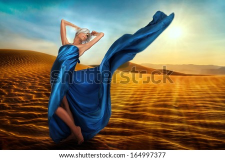 Blond pretty woman wrapped in blue satin - stock photo