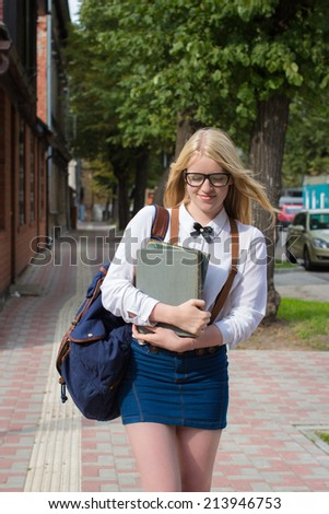 Blond school girl with nerd glasses on her way to school / home. Selective focus. - stock photo