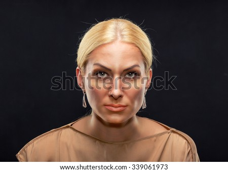 Blond serious adult woman looking at you over black - stock photo
