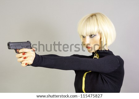 Blond sexy girl with gun - stock photo