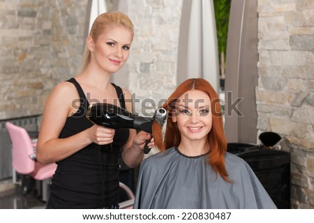blond stylist drying redhead woman hair in salon. happy female giving new hair style to woman and looking into camera - stock photo