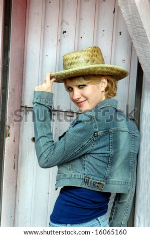 Blond teen poses besides a pink painted rustic doorway. - stock photo