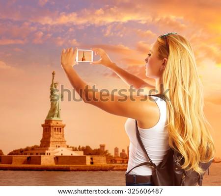 Blond tourist taking photo to Statue of Liberty in New York photomount - stock photo