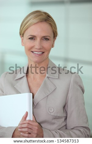 Blond woman carrying computer - stock photo