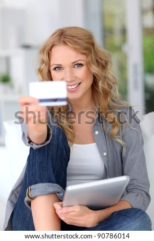 Blond woman doing online shopping with digital tablet - stock photo