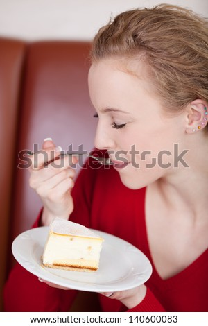 blond woman enjoying cheese cake in a coffee house - stock photo