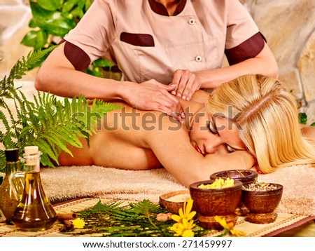 Blond woman getting massage in tropical spa. Fern in foreground - stock photo