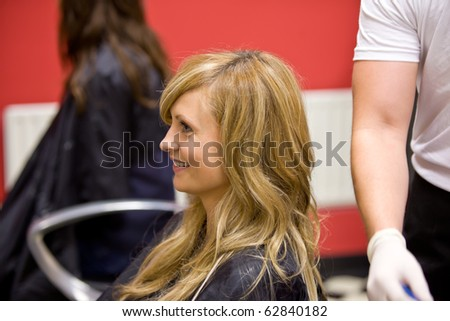 Blond woman having her hair dye in a hairdressing salon - stock photo