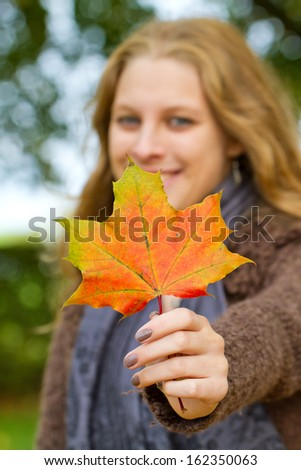 Blond woman holding a autumn leaf - stock photo
