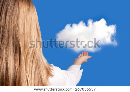 blond woman holding a white cloud over clear blue sky - stock photo