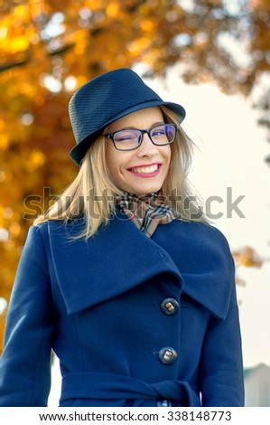 Blond woman in a blue hat and glasses on the background of yellow foliage - stock photo