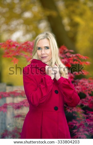 blond woman in a red coat standing beneath colorful trees in autumn - stock photo