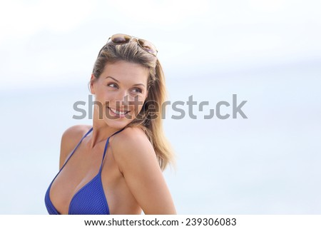 Blond woman in bikini with eyeglasses posing by the beach - stock photo