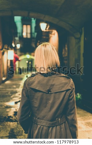 Blond woman in raincoat walking alone outdoors at night - stock photo