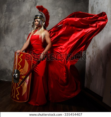 Blond woman in Roman red fluttering dress holds sword and shield. - stock photo