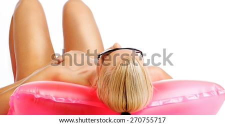Blond woman in sunglasses lying on water mattrass. Isolated on white - stock photo