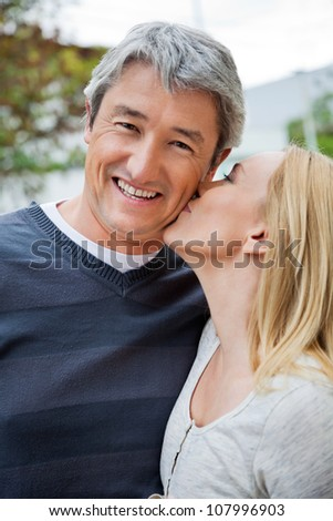 Blond woman kissing a cheerful middle aged man - stock photo