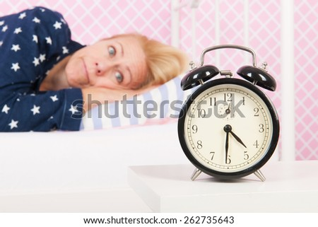 Blond woman of mature age with insomnia and big alarm clock - focus point on clock - stock photo