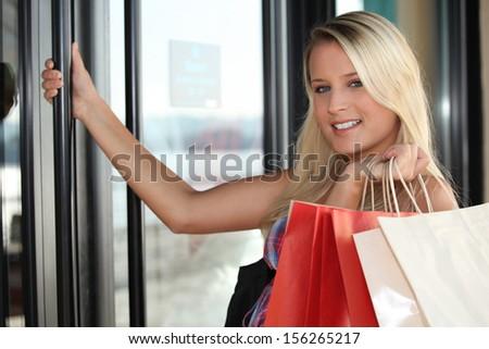 Blond woman opening shop door - stock photo