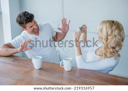Blond woman photographing her husband with a mobile fun as he playfully holds his hands in the air while grinning at her - stock photo
