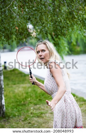 blond woman playing badminton in a park - stock photo