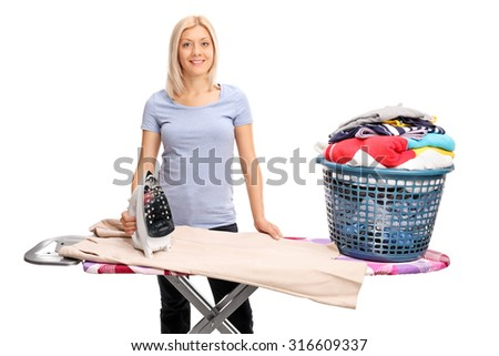 Blond woman posing behind an ironing board with a basket full of clothes on it isolated on white background - stock photo