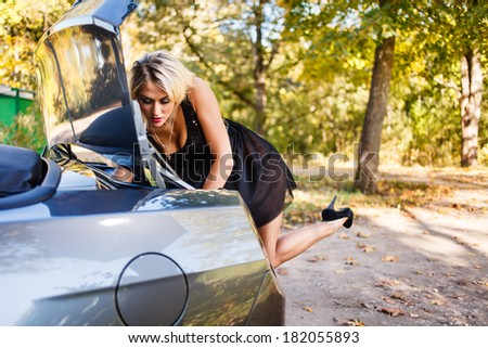 Blond woman searching something in  a car trunk. - stock photo