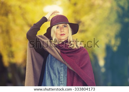 blond woman standing beneath colorful trees in autumn - stock photo