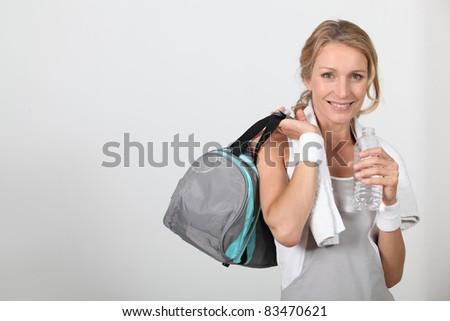 Blond woman wearing sportswear holding water bottle with bag over shoulder - stock photo