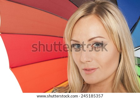 Blond woman with a smile under an umbrella - stock photo