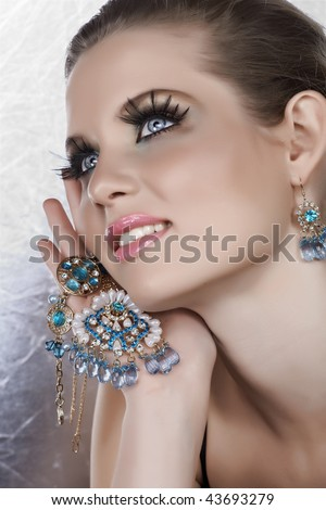 Blond woman with long fake lashes holding pearl and blue stones golden jewelry with happy expression from 16 Bit RAW - stock photo