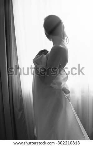 Blond young beautiful woman having fun hiding under white sheet standing on light window copy space background. Black and white portrait  - stock photo
