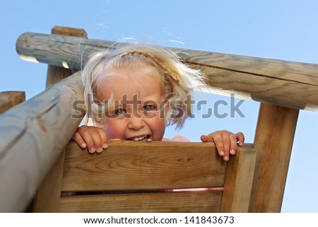Blond young child playing in the play ground - stock photo