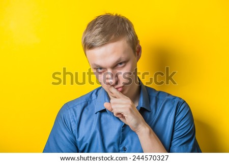 Blond young man holding his finger at the mouth, quiete, calme. Close portrait. Gesture. Isolated yellow background. photo - stock photo