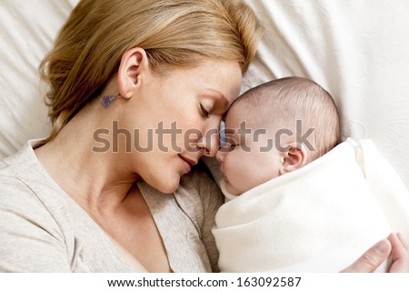 blond young mother with her baby lying in the bed - stock photo