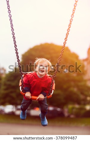 Blond young toddler boy swinging at children playground. Happy child having good time outdoors. - stock photo